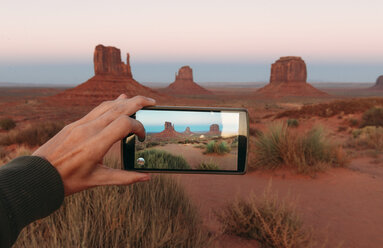 USA, Utah, Monument Valley at sunset, woman's hand taking a photo with mobile - GEMF02873