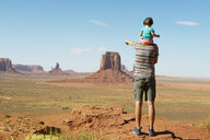 USA, Utah, Monument Valley, Father traveling with baby, girl on shoulders and pointing to Monument Valley landscape - GEMF02879