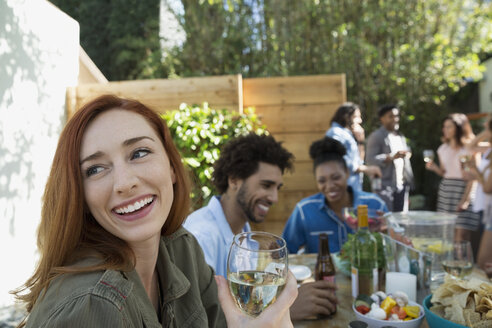 Smiling woman drinking white wine at patio table - HEROF27426
