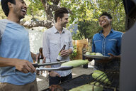 Smiling friends drinking beer and barbecuing corn cobs - HEROF27429
