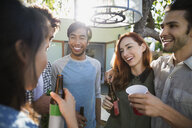 Smiling friends talking drinking beer on sunny patio - HEROF27435