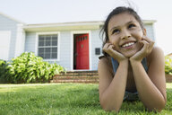Smiling girl laying in grass in front yard - HEROF27459