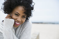 Portrait smiling woman curly black hair at beach - HEROF27462