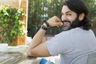 Portrait smiling bearded man at patio table turning - HEROF27481