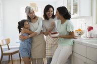Multi-generation women laughing in kitchen - HEROF27508