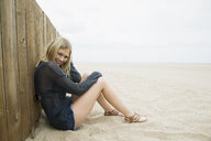 Portrait smiling blonde woman sitting at beach wall - HEROF27514