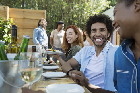 Friends laughing eating and drinking at patio table - HEROF27529