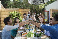 Friends toasting wine glasses at patio table - HEROF27532