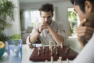 Focused men playing chess at table - HEROF27538