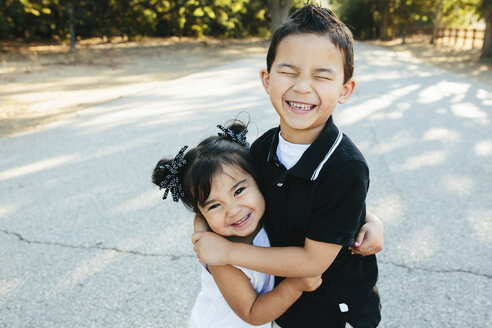 Portrait of happy sister embracing brother while standing on road in park - CAVF62718