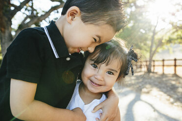 Close-up of happy brother embracing cute sister while standing against trees in park - CAVF62721