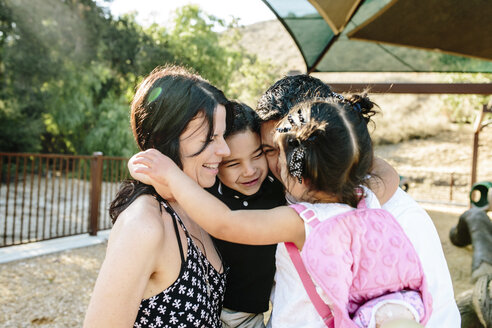 Happy multi-ethnic parents embracing children while standing in park - CAVF62727