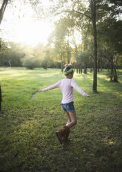 Rear view of girl with arms outstretched dancing on grassy field against trees in park - CAVF62730