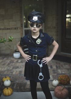Portrait of confident girl in police costume with hands on hip standing against house during Halloween - CAVF62733