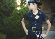 Confident girl wearing police costume with hands on hip standing against plants in yard during Halloween - CAVF62736