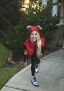 Portrait of happy girl wearing Halloween costume standing on footpath against plants in yard during sunset - CAVF62739