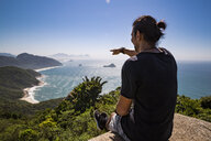 Tourist pointing at sea while sitting on cliff against blue sky during sunny day - CAVF62781