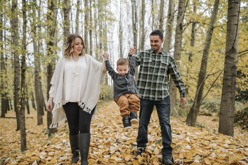 Playful parents swinging son while holding his hands in forest during autumn - CAVF62802
