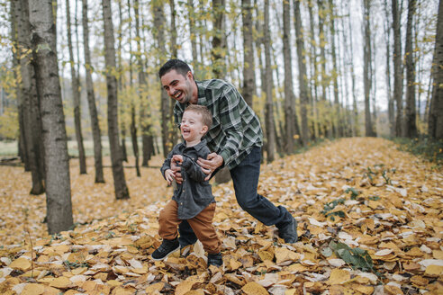 Cheerful father and son playing on dry leaves in forest during autumn - CAVF62805
