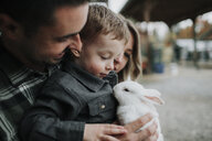Close-up of cute son playing with rabbit by parents at farm - CAVF62826