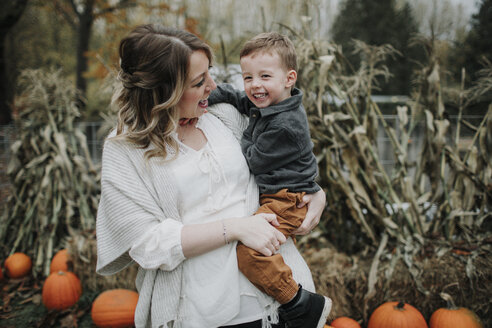 Cheerful mother carrying cute son on pumpkin patch during autumn - CAVF62829