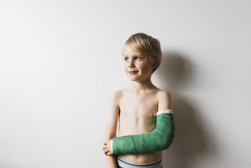 Thoughtful shirtless boy with broken arm looking away while standing against wall at home - CAVF62832