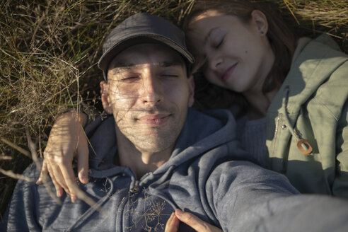High angle close-up of couple sleeping on grassy field - CAVF62847