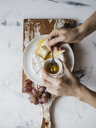 Cropped hands of woman eating breakfast served on wooden tray - CAVF62862