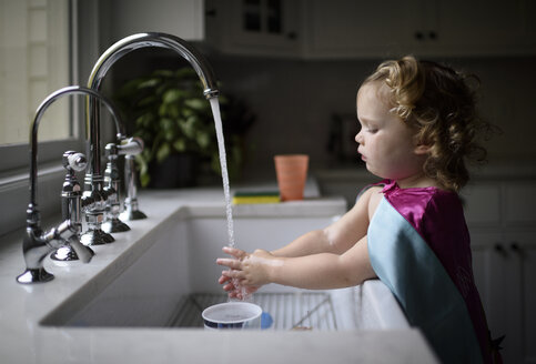 Side view of girl wearing pink cape washing hands in kitchen sink while standing at home - CAVF62871