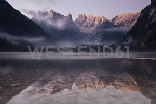 Scenic view of mountains reflecting on calm lake against sky during sunrise - CAVF62880 - Cavan Images/Westend61