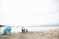 Family making sandcastle on sunny beach - HEROF27664