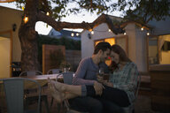 Affectionate couple relaxing drinking wine on patio - HEROF27685