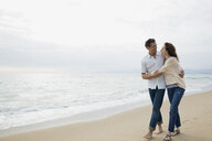 Affectionate couple hugging and walking on beach - HEROF27706