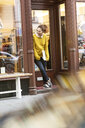 Young woman standing in door of a fashion store, holding laptop - PESF01513
