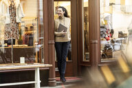 Mature woman standing in door of a fashion store, holding laptop - PESF01516