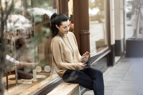 Mature woman sitting in front of her fashion store, using tablet - PESF01519