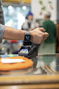 Customer paying contactless with his smartwatch - PESF01528