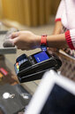 Customer paying contactless with her smartwatch - PESF01537