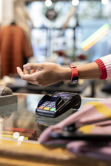 Customer paying contactless with her smartwatch - PESF01540