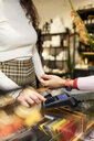 Customer paying contactless with her smartwatch - PESF01543