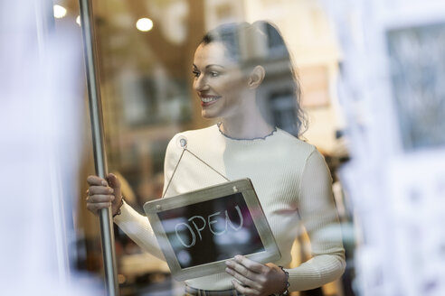 Mature woman standing in shop , smiling, with open sign hanging in window - PESF01555