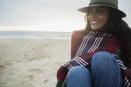 Smiling brunette woman hat wrapped in blanket beach - HEROF27723