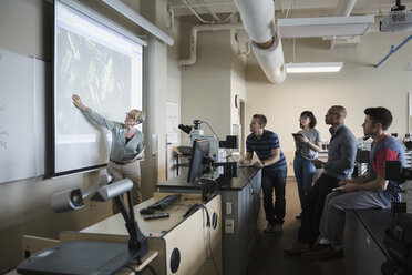 Science professor leading lesson at projection screen classroom - HEROF27735