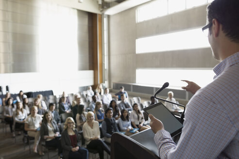 Professor with digital tablet speaking to students auditorium - HEROF27786