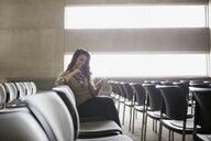 Smiling student texting with cell phone auditorium seat - HEROF27801