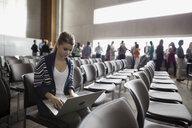 Student using laptop in auditorium seat - HEROF27807