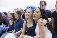 Smiling fans in blue hugging bleachers sports event - HEROF27810