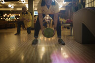 Woman bowling between legs at bowling alley - HEROF27822