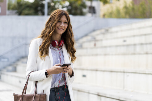 Young businesswoman commuting in the city, using smartphone - GIOF05776