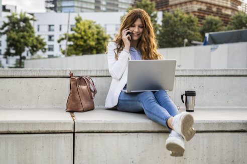 Young businesswoman sitting on bench in the city, using laptop, talking on the phone - GIOF05782